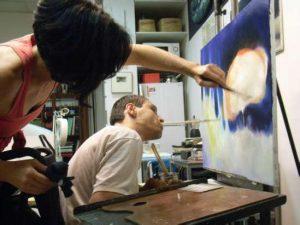 El pintor Francisco Javier Planells pintando uno de sus cuadros con la boca